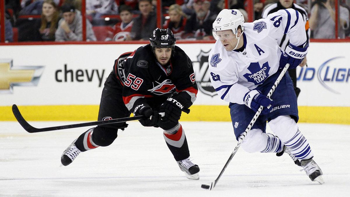 Carolina Hurricanes' Chad LaRose (L) battles the Toronto Maple Leafs' Phil Kessel for the puck during the second half of their NHL hockey game in Raleigh, North Carolina December 29, 2011.