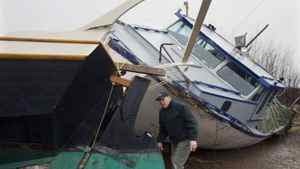 Chuck Hunziker inspects the stern of his friend Tam Flemming's 45-foot schooner in Barrachois, N.S. on Wednesday, Dec. 22, 2010. Both the schooner and the fishing boat floated off their cradles after a storm surge hit the marina. The third Atlantic storm in a month crashed through seawalls, flooded wharfs and damaged homes along the east coast.