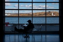 Georges Island is seen in the Halifax Harbour as a man is silhouetted while reading in the Halifax Seaport Farmer's Market on the waterfront in Halifax on Tuesday, Feb. 27, 2018. Darren Calabrese/The Globe and Mail