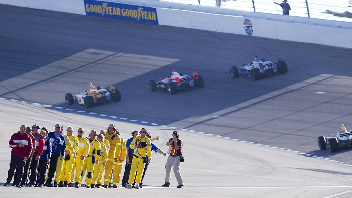 Officials and safety workers watch as drivers take five tribute laps in honor of Dan Wheldon.