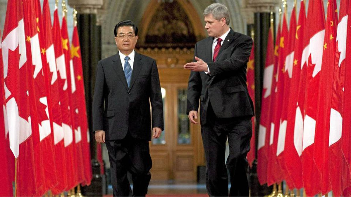 Canadian Prime Minister Stephen Harper gestures to Chinese President Hu Jintao as they walk through the Hall of Honour on Parliament Hill in Ottawa on June 24, 2010.