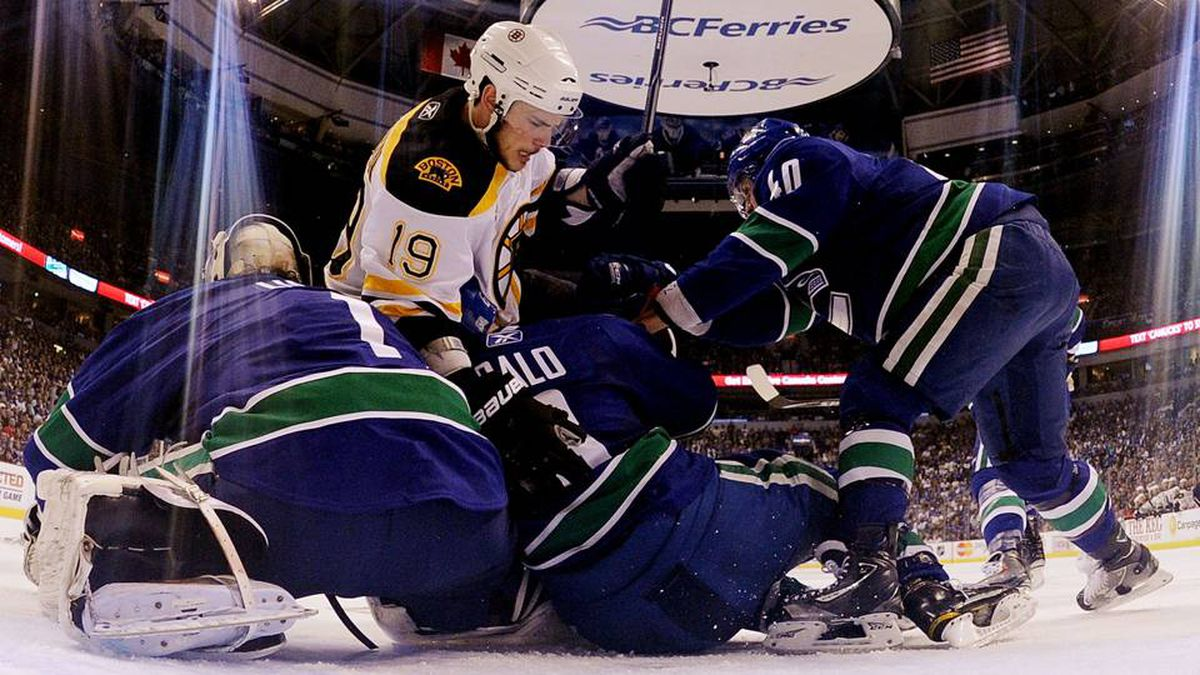 Tyler Seguin of the Boston Bruins collides with Roberto Luongo, Sami Salo and Maxim Lapierre of the Vancouver Canucks during Game 5.