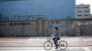 A woman rides her bicycle in front of a closed factory in Wenzhou. Shadow banking in the entrepreneurial city has begun to alarm China's regulators, perturbed by media attention to a string of incidents involving corporate bosses running into hiding after failing to repay high-interest loans.