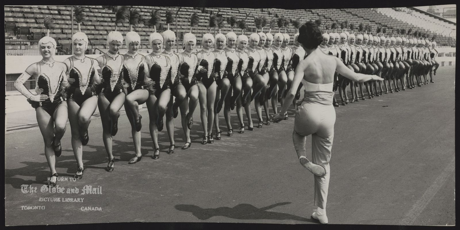 CNE GRANDSTAND SHOW JULY 30, 1957 -- JUST 3 WEEKS TO GO BEFORE OPENING SHOW -- Fifty gorgeous girls highkick their way through practice session for grandstand show which opens in three weeks. The Canadettes wear costumes of satin latex and nylon net as Midge Arthur, choreographer and wife of Jack Arthur, show's producer, shows them how NOT to dance. Photo by Harry McLorinan / The Globe and Mail Originally published July 31, 1957, page A7.