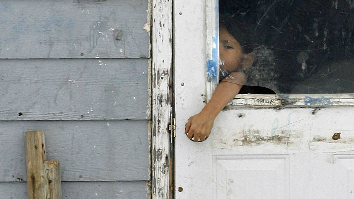 A child reaches through a broken window to open the door of a house on the Pikangikum reserve in Northwest Ontario on Jan. 5, 2007.