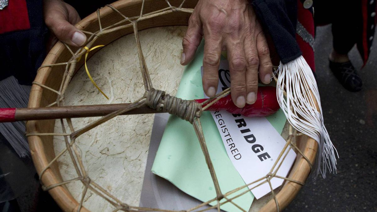 Chief Martin Louie tucks his proxy slip in his drum after emerging from the Enbridge annual meeting.