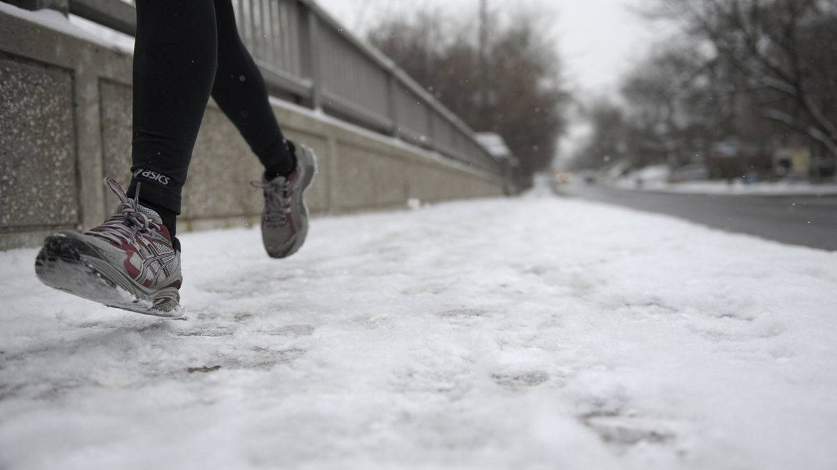 A jogger navigates a snow covered sidewalk on Spadina Rd south of St. Clair Ave. West after Toronto had it's first noticeable snowfall of the season on Dec 6 2010.