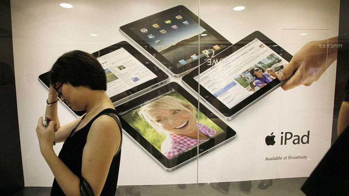 A woman waits in line to buy an Apple iPad at an Apple reseller retail shop during the launch of the devise in Hong Kong on Friday, July 23, 2010.