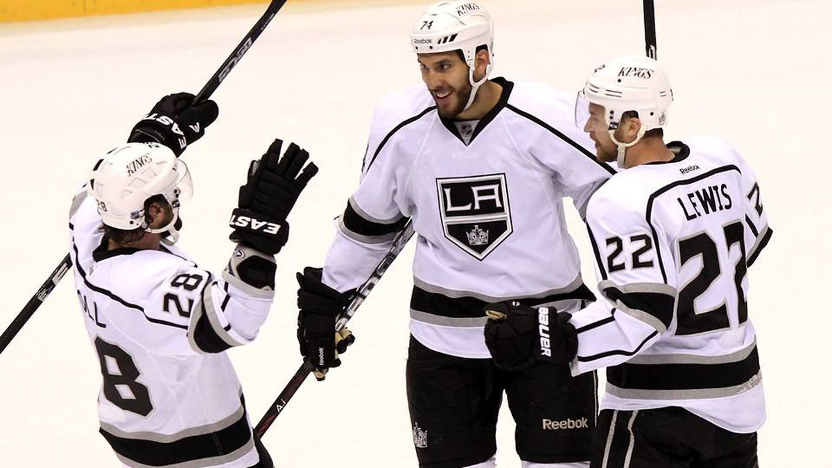 Los Angeles Kings' Dwight King (74) celebrates his empty net goal against the Phoenix Coyotes, and his second goal of the game, with teammates Jarret Stoll (28) and Trevor Lewis (22) during the third period of Game 1 of the NHL hockey Stanley Cup Western Conference finals, Sunday, May 13, 2012, in Glendale, Ariz.