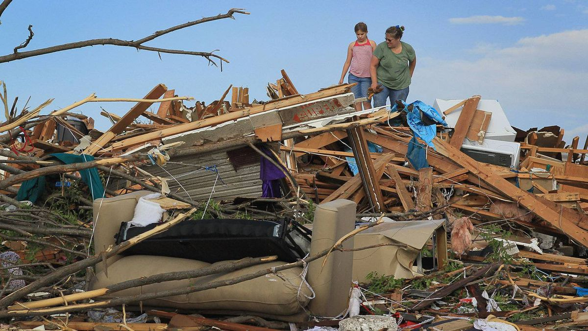 Maddie Meek, 9, (L) and her mother Dina Meek salvage what they can from her sister-in-law's home after it was destroyed when massive tornado passed through the town killing at least 116 people on May 24, 2011 in Joplin, Missouri. Authorities were prepared to find more bodies in the town of 50,000 people.