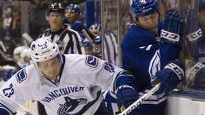 Vancouver Canucks' Alexander Elder (left) puts Toronto Maple Leafs' Colby Armstrong into the boards as they battle for control of the puck during second period NHL hockey action in Toronto on Saturday December 17, 2011. THE CANADIAN PRESS/Pawel Dwulit