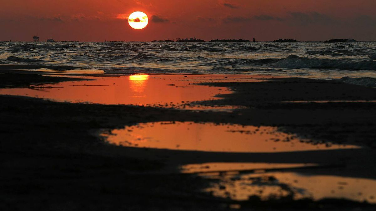 The sun rises over an oil-soaked beach on May 23, 2010 on Grand Isle, Louisiana.