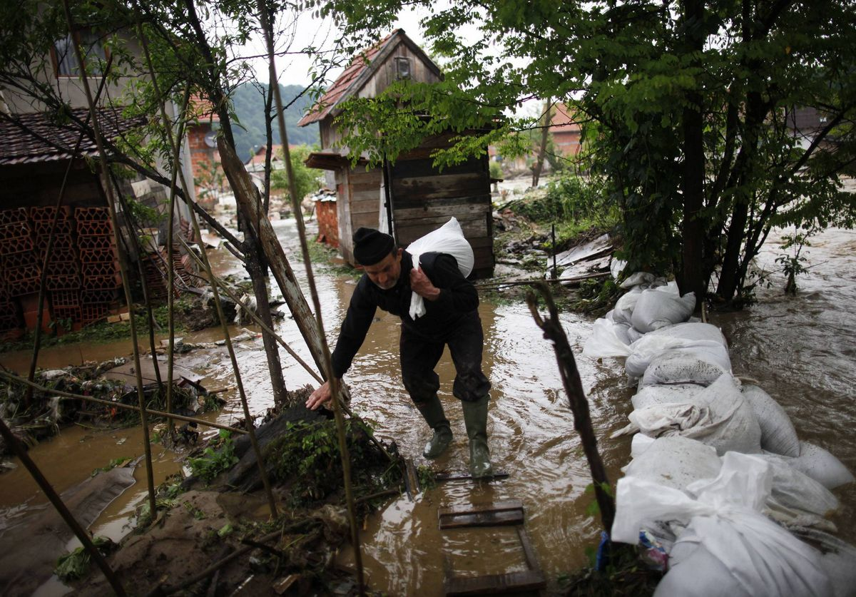 A man carries a bag during floods in Potocari, near Srebrenica. The eastern part of Bosnia has been flooded for the last two days and about 600 houses are underwater according to local media.