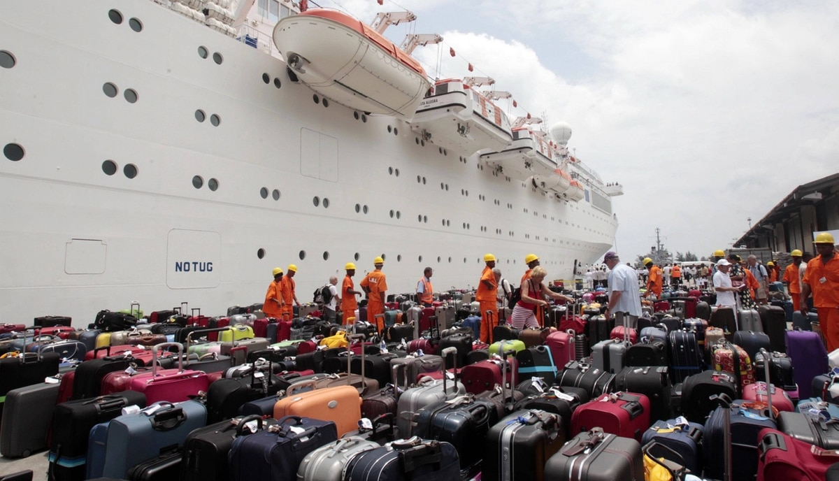 Passengers of the Costa Allegra cruise ship look for their baggage upon their arrival at Victoria's harbor, Seychelles Island, Thursday, March 1, 2012. A disabled cruise ship carrying more than 1,000 people docked in the island nation of the Seychelles Thursday after three days at sea without power since a fire broke out in the generator room on Monday.
