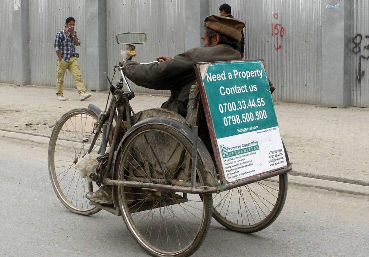A man rides a pedicab that carries an advertisement for properties in Kabul, Afghanistan.