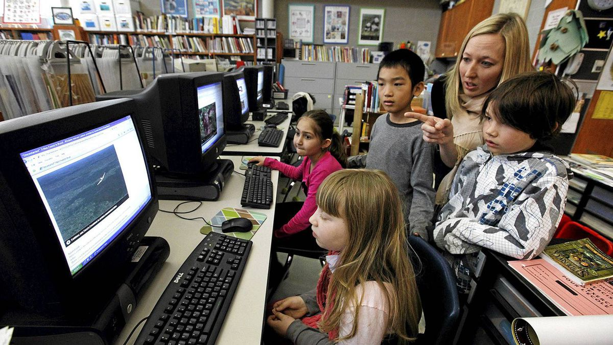 Jessica Shanani, 8, Mia Miric, 8, Hao Chen Yu, 9, teacher Kathleen Tilly and Aidan Isaac Ley, 8, discuss a video in the library at Eglinton Public School in Toronto.