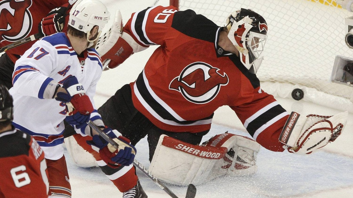 New York Rangers' Brandon Dubinsky, left, watches a shot by teammate Ryan Callahan go in for a goal past New Jersey Devils' Martin Brodeur during the second period of Game 6 of the NHL hockey Stanley Cup Eastern Conference finals Friday, May 25, 2012, in Newark, N.J.