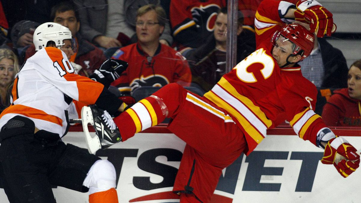 Philadelphia Flyers' Brayden Schenn, left, checks Calgary Flames' Cory Sarich along the boards during second period NHL hockey action in Calgary, Alta., Saturday, Feb. 25, 2012.THE CANADIAN PRESS/Jeff McIntosh