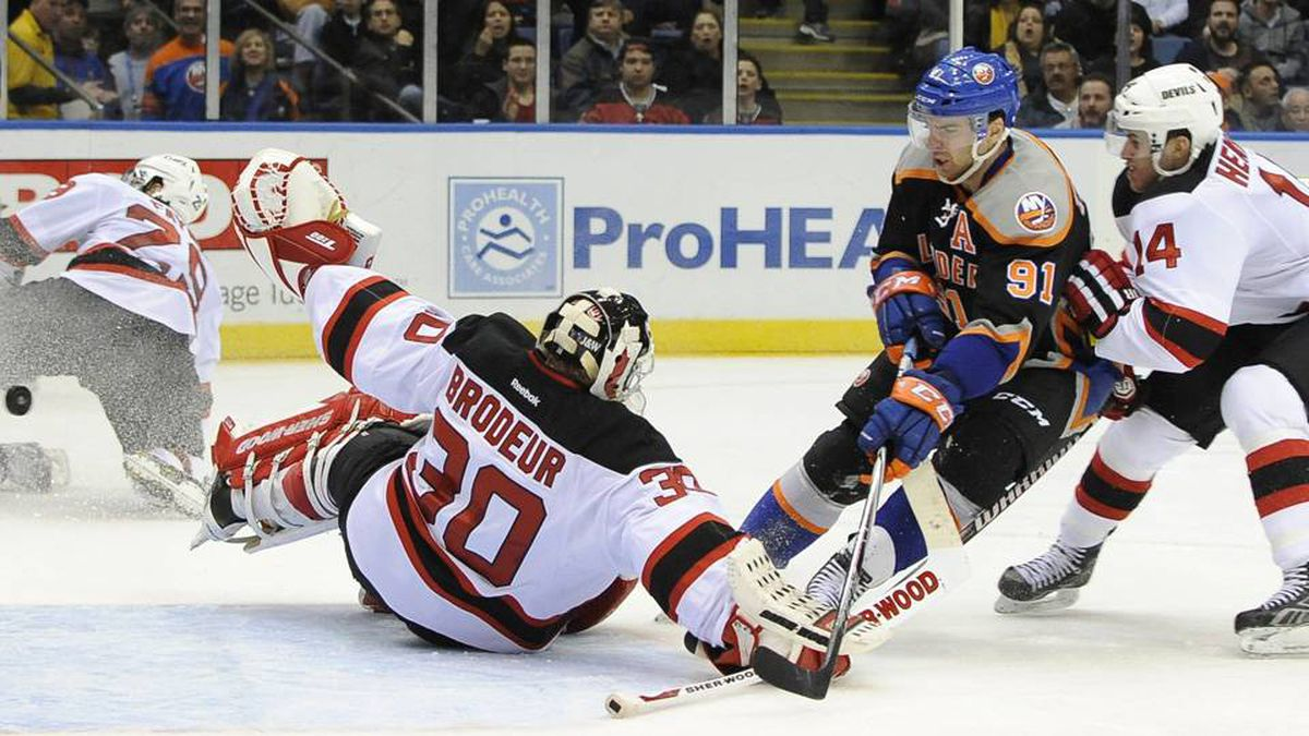 New Jersey Devils goalie Martin Brodeur (30) blocks a shot on goal by New York Islanders' John Tavares (91) as Devils' Adam Henrique (14) defends from behind in the second period of an NHL hockey game on Sunday.