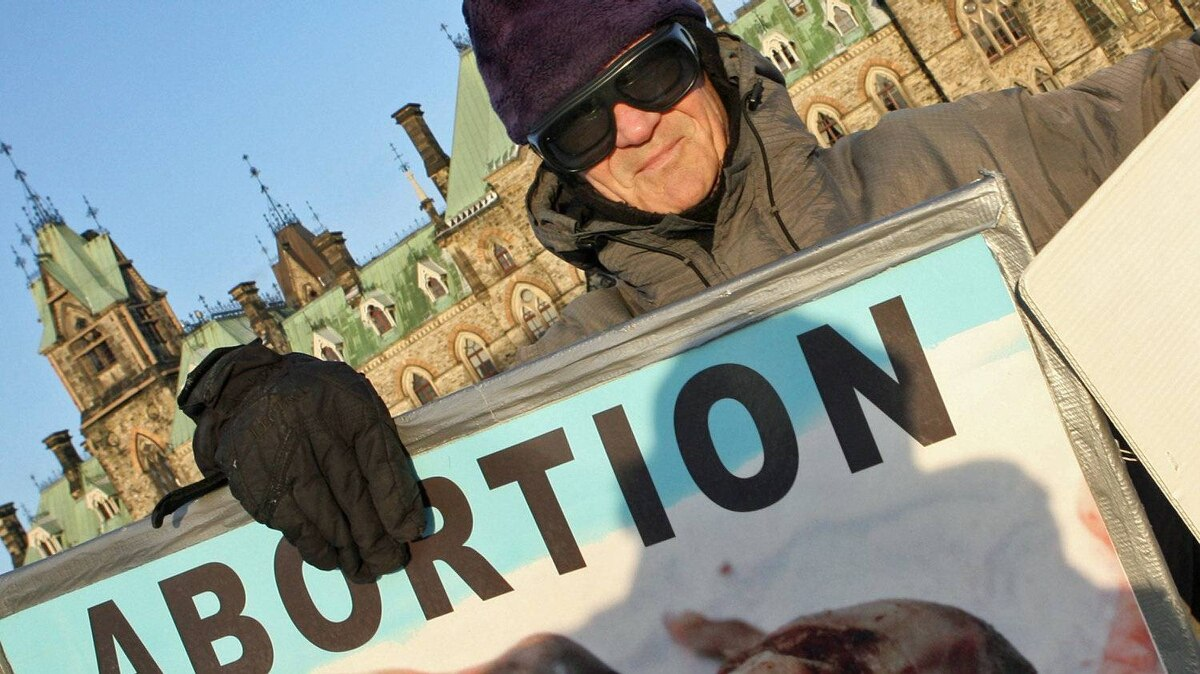 A protester waves anti-abortion placards on Parliament Hill in 2006.