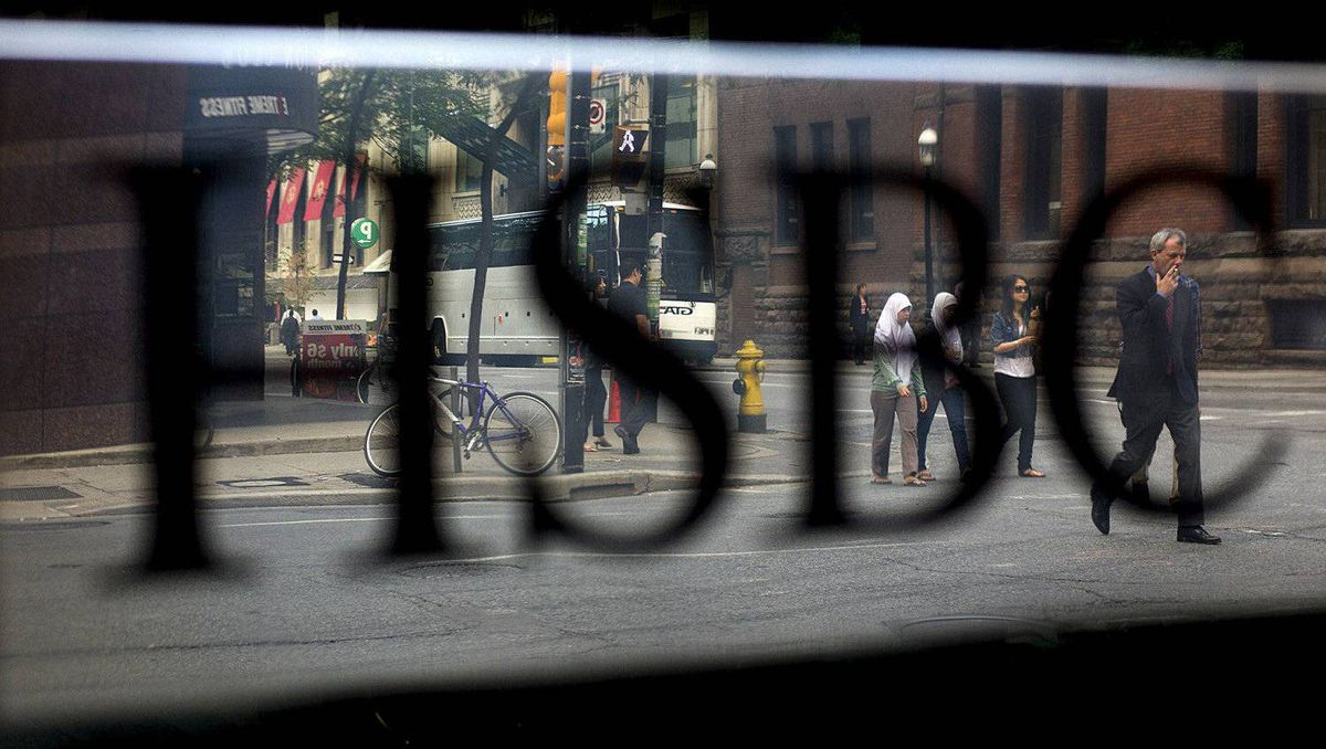 Pedestrians pass in front of HSBC Holdings Plc signage displayed near Bay Street in Toronto, Ontario, Canada, on Monday, Aug. 29, 2011. Bay Street is the center of Toronto's Financial District and is often used as a metaphor to refer to Canada's financial industry. Photographer: Brent Lewin/Bloomberg
