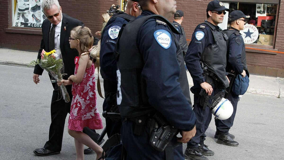 A girl with a bouquet of flowers is escorted past police officers before the arrival of Britain's Prince William and his wife Catherine, Duchess of Cambridge, at the Institut de tourisme et d'hotellerie du Quebec in Montreal July 2, 2011.
