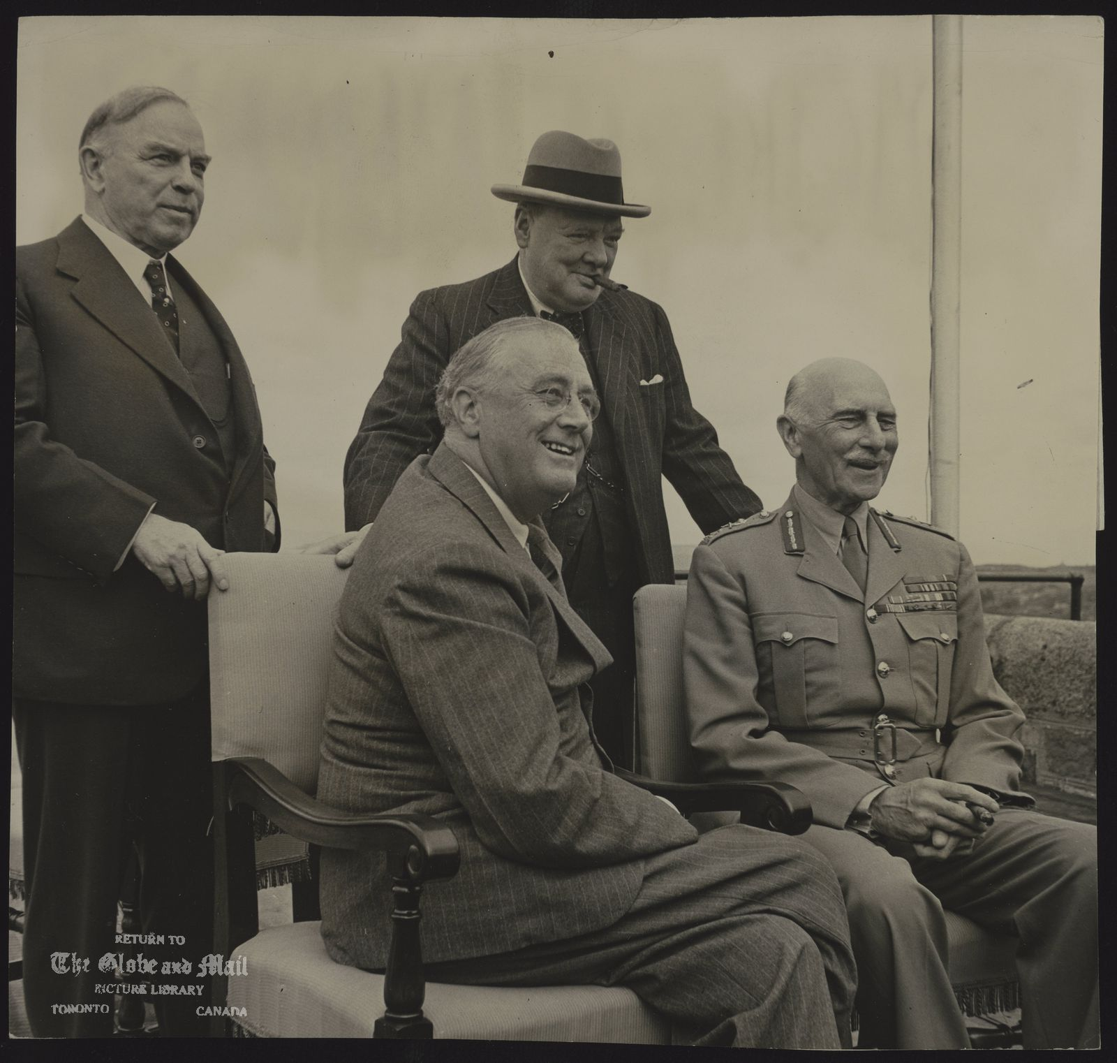 QUEBEC CONFERENCE 1943 BIG THREE OF UNITED NATIONS TOGETHER IN QUEBEC CITY QUEBEC, August 18th ? Within the ancient walls of Quebec's historic Citadel, summer residence of Canada's Governor General, the heads of Great Britain, Canada and the United States sat in conference today with their combined chiefs of staff, In the afternoon they came out on the terrace overlooking the St. Lawrence to pose for photographers and newsreel cameramen. President Roosevelt, left, sat beside the Earl of Athlone, Governor General of Canada, while behind them stood Prime Minister Mackenzie King and Prime Minister Winston Churchill. Concerned about the safety of photographers who climbed up on the parapet to make their pictures, Mr. King and Mr. Churchill warned them several times not to slip and fall off.