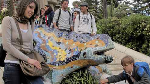 Gaudi's mosaic dragon fountain at the entance to Park Guel in Barcelona is a popular place for tourists.