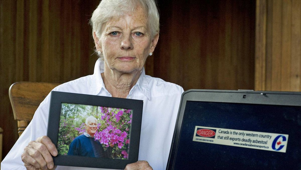 Michaela Keyserlingk, whose husband Robert died of asbestos-related cancer, displays his photo and a banner ad she created to put pressure on the Conservative government at her home in Labelle, Que., on Aug. 13, 2011.