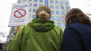 Two women stand in front of BC Hydro headquarters as they protest BC Hydro's use of smart meters in Vancouver, BC, Feb. 29, 2012.