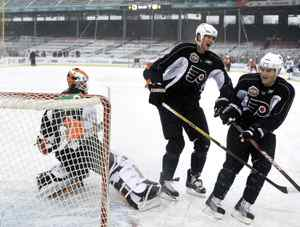 Philadelphia Flyers' Chris Pronger, center, laughs with Matt Carle, right, during a drill against goalie Michael Leighton during practice on the outdoor rink at Fenway Park in Boston on Thursday, Dec. 31, 2009. (AP Photo/Elise Amendola)