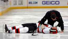 Head trainer Richard Stinziano of the New Jersey Devils goes to the aid of Patrik Elias of the Devils who lies motionless on the ice after being checked by Ryan Wilson of the Colorado Avalanche during NHL action at the Pepsi Center on January 16, 2010 in Denver, Colorado.