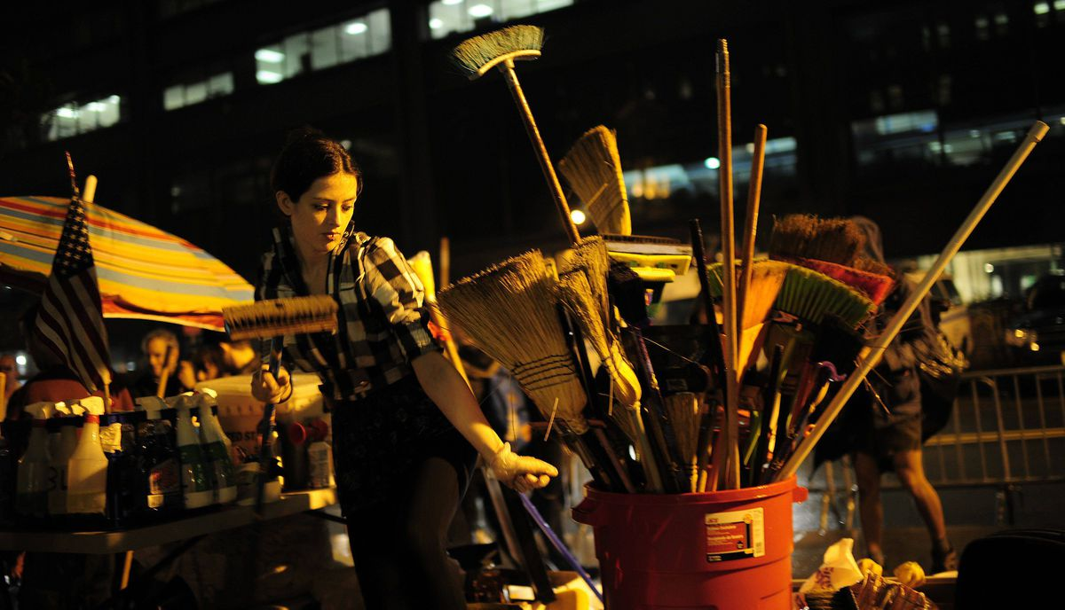 A member of Occupy Wall Street picks up a broom to clean Zuccotti Park near Wall Street.