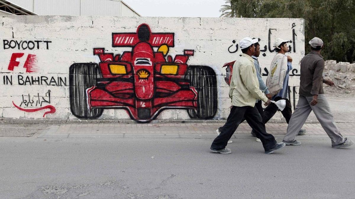 Men walk past anti-Formula One graffiti in the village of Barbar in Bahrain.