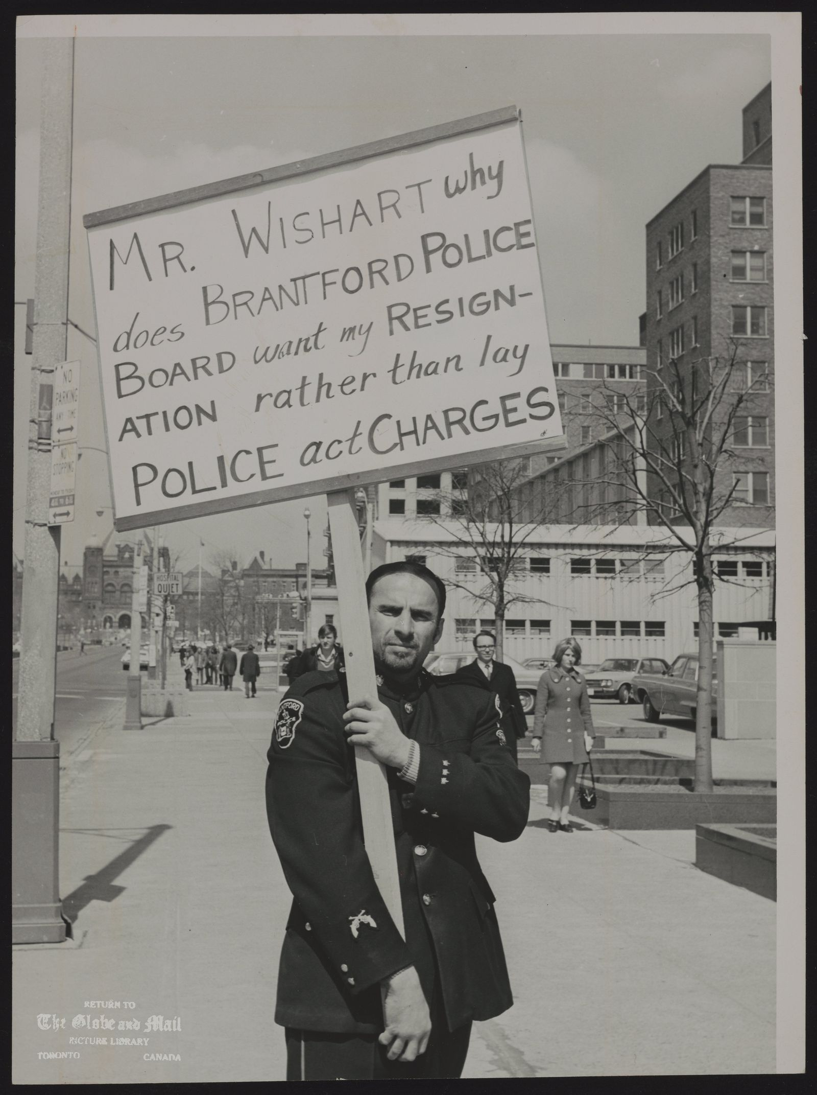 The notes transcribed from the back of this photograph are as follows: BRANTFORD city Police Department Constable Lester Lolli [Constable Lester Lolli of Brantford as he paraded outside the Ontario Police Commission offices with complaints of corruption inside his force]