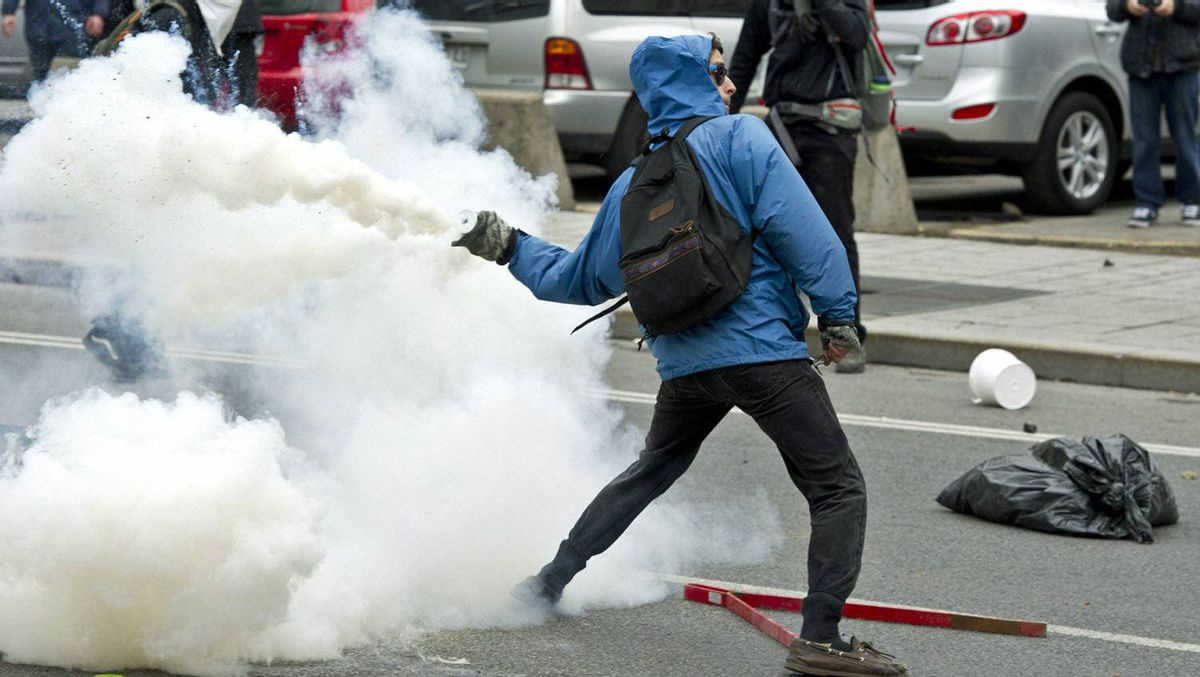 A demonstrator throws tear gas canister back towards the police line during a student demonstration outside the Montreal Convention Centre against hikes to university and college tuition fees on April 20, 2012 in Montreal.