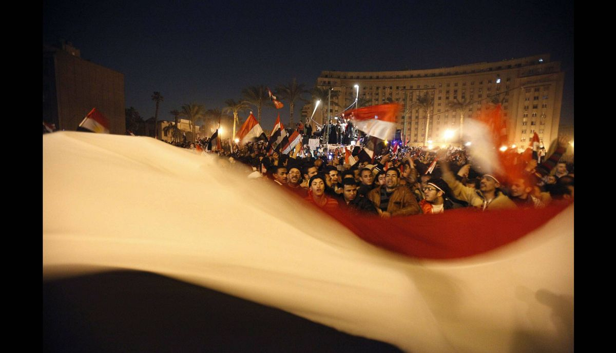 Egyptian youths wave a large Egyptian flag as they celebrate the announcement of Egyptian President Hosni Mubarak's resignation at Tahrir Square in Cairo Feb. 11, 2011.