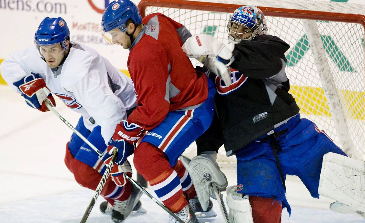 Montreal Canadiens' goaltender Carey Price, right, collides with Canadiens' Tom Pyatt, centre, and Frederic St-Denis during training camp in Brossard, Que., Saturday, Sept., 18, 2010. THE CANADIAN PRESS/Graham Hughes