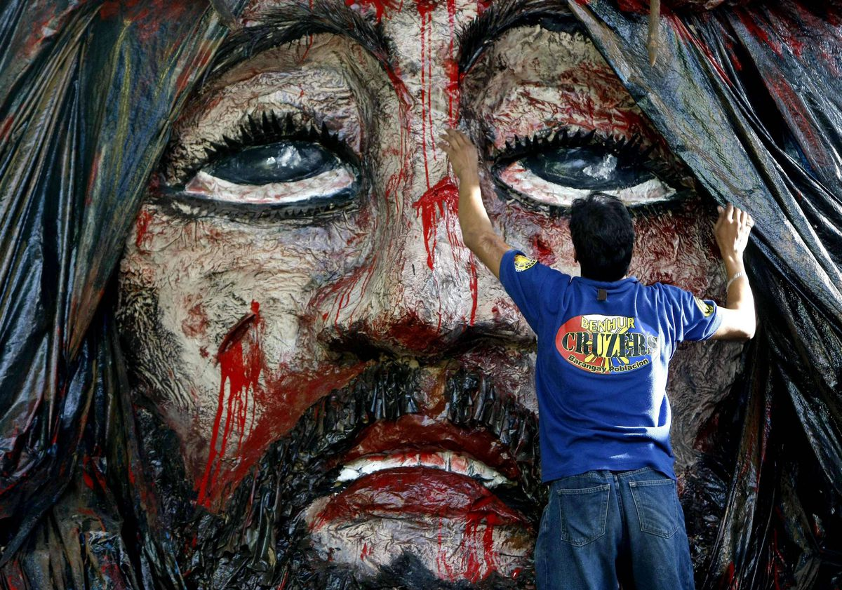 Filipino self-taught artist Ronald Bautista works on his version of the Passion of Jesus Christ Wednesday, April 4, 2012 at the financial district of Makati city, east of Manila, Philippines in his neighborhood's observance of Holy Week. The giant art installation, made of recyclable materials, has attracted a number of local and foreign devotees.