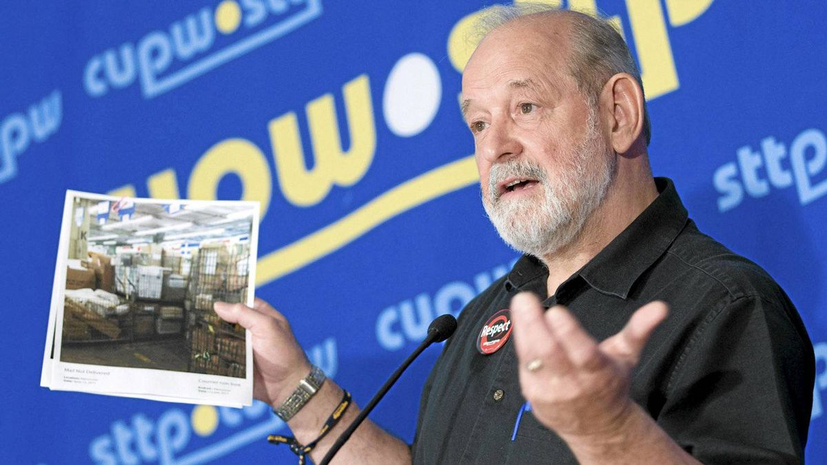 CUPW National President and Chief Negotiator Denis Lemelin holds up a picture of mail sitting at a Canada Post facility as he speaks with the media in Ottawa, Monday June 13, 2011.