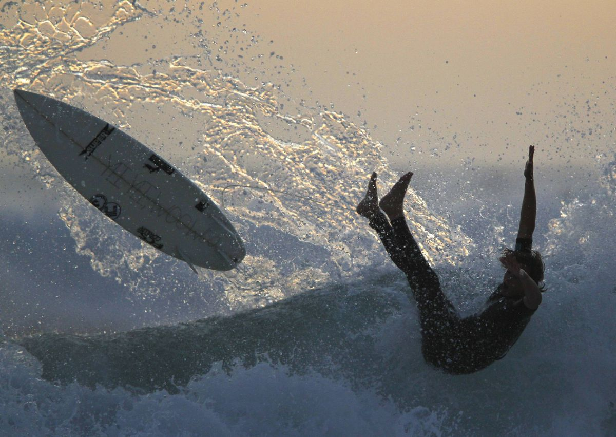 A surfer falls off his board while riding after sunset in Cardiff, California May 14, 2012.