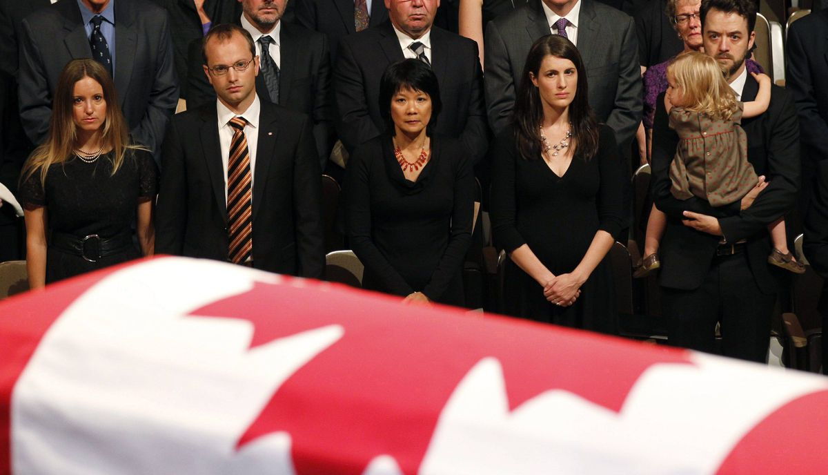 Family members watch as the coffin of the late NDP leader Jack Layton is carried into at Roy Thomson Hall.