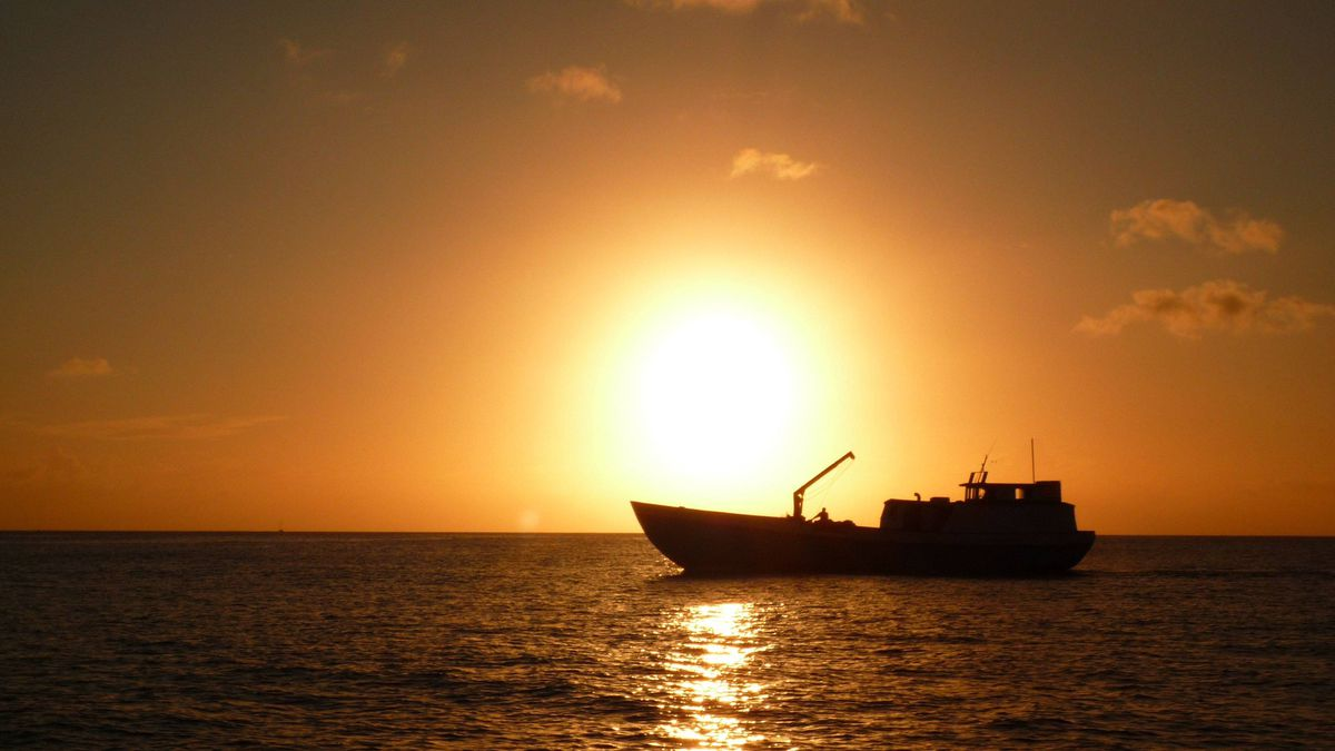 As the sun sets over the Caribbean Sea, a fishing boat heads home to a Grenada harbour.