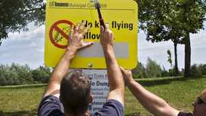 Municipal workers post signs prohibiting kite flying at Miliken Park, in Scarborough last summer.