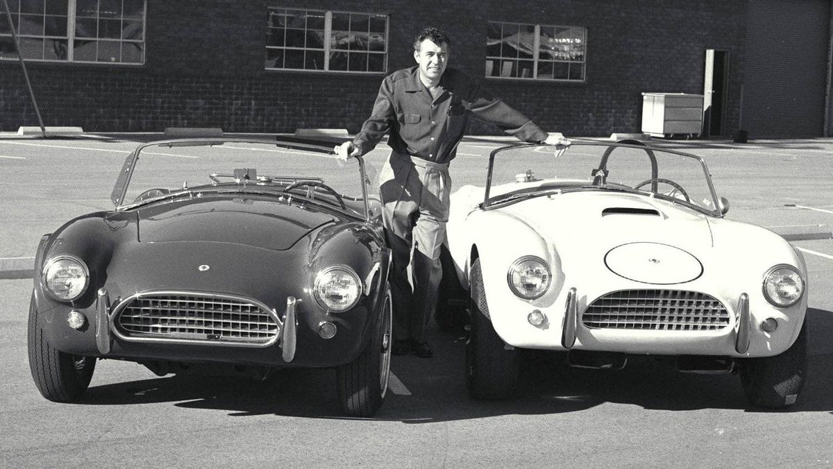 Carroll Shelby poses with his new 1964 production Cobra and his new Cobra race car in California.