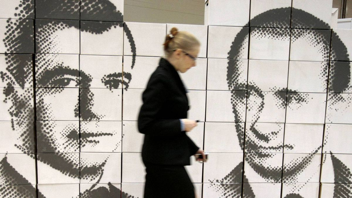 A woman walks by a panel made of cardboard boxes, displaying Russia�s President Dmitry Medvedev, left, and Prime Minister Vladimir Putin, at an innovation technologies exhibition in the city of Rostov-on-Don.