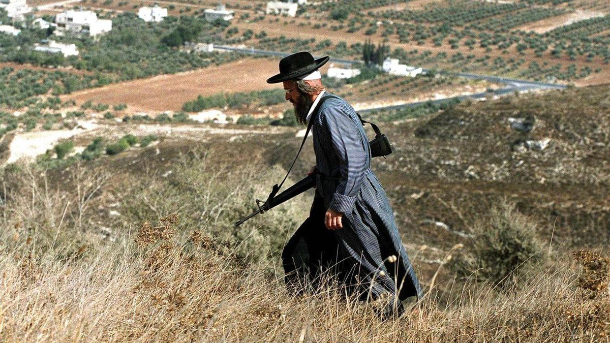 An armed ultra-orthodox Jewish settler walks in the mountains overlooking the Palestinian village of Burin in the West Bank.