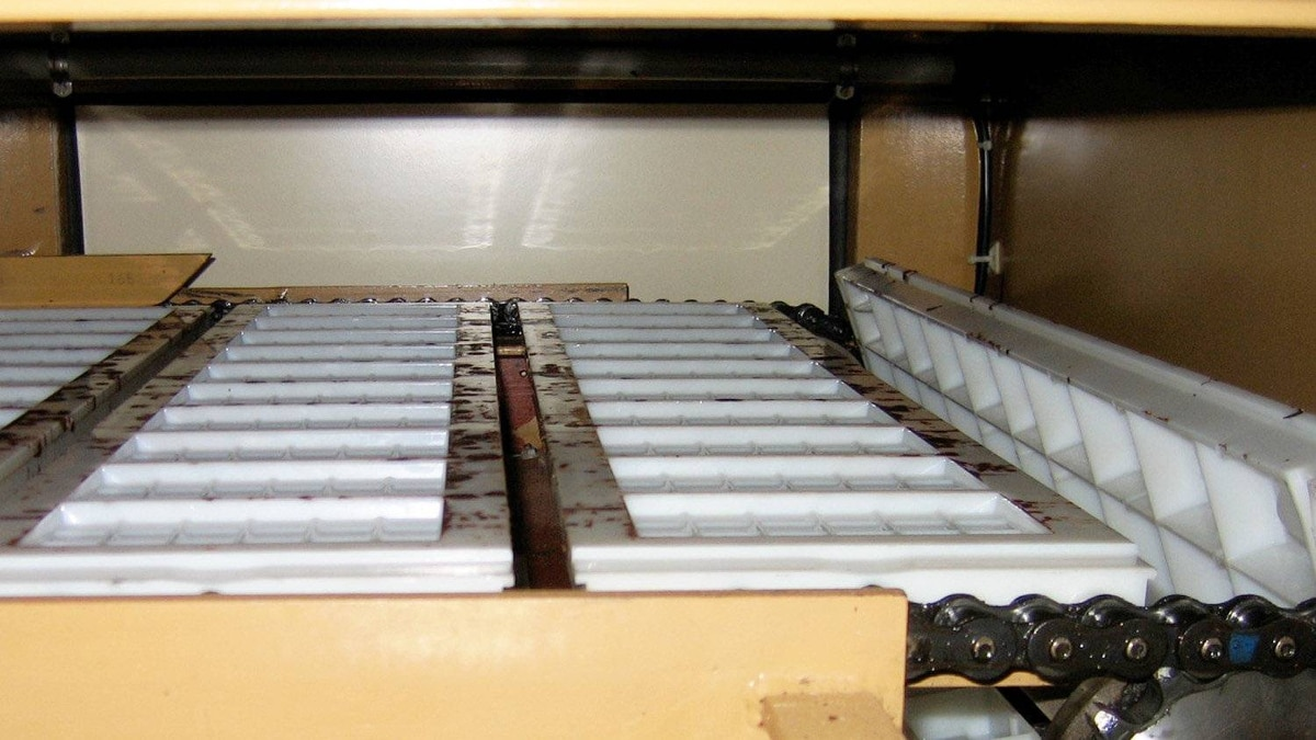 The empty molds move through the manufacturing facility's line to be filled with the chocolate mix that will form Camino's 100-gram bars.