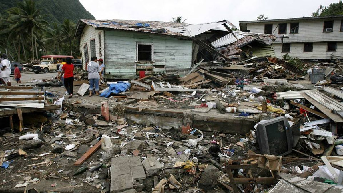 Villagers walk around debris and a house that was smashed by a tsunami in Pago Pago Harbor after an earthquake on the island of American Samoa, September 30, 2009.