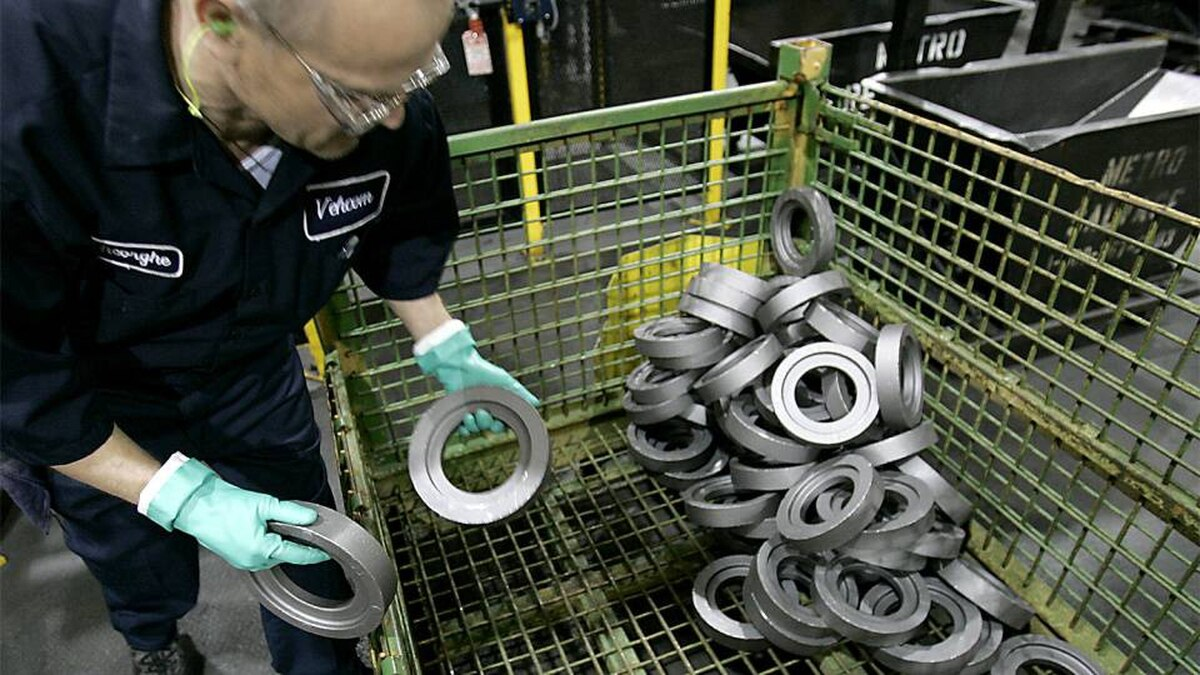 An employee of Linamar loads gear castings at a plant in Guelph, Ont.